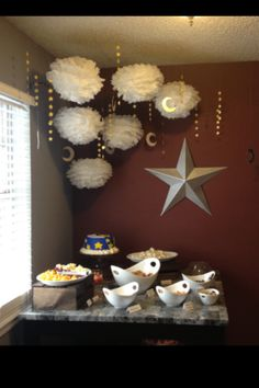 Moon and Stars party or shower theme. The star strands were made with a star punch from the craft store and different shades of yellow paint sample strips from Wal Mart. I hot glued the stars to fishing line back-to-back to create them. The moons are cardboard sprayed with silver/gold paint.