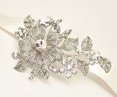 This gorgeous, dramatic ribbon bridal headband features an elegant floral design with one rhinestone flower surrounded by leaves and smaller jeweled flowers on a satin ribbon.  This beautiful comb is perfect for your glamorous, elegant wedding day look.  Choose white or ivory ribbon.