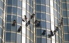 The tower has more than 26,000 glass panes. Here, a window-cleaning crew works at a dizzying height.