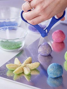 Roll a sugar cookie dough ball in colored sugar. Snip it in half with scissors, then snip each half into three petals. Gently spread the petals apart and lay flat. Put a round colored candy in the center for the perfect touch!