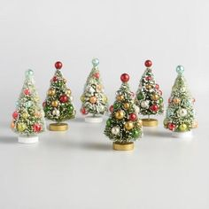 Create a festive holiday display with our retro bottlebrush trees, covered with chunky glitter and sitting on circular wood bases. Each set - one in traditional Christmas colors, the other in vintage-inspired pastels - is studded with antiqued ball ornaments for plenty of yuletide sparkle.