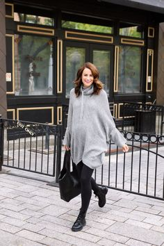 the miller affect wearing a grey poncho sweater from Walmart