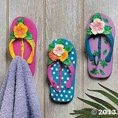 Use cheap flipflops and wall hooks, paint them up and away you go! Lovely idea for kids pool area