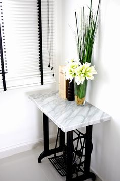 Black and white venetian blinds, marble-top sewing machine and fresh flowers