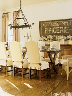 """The breakfast room features an antique French trestle table from Erika Reade and an 1870s French bakery sign from Ainsworth-Noah. """"I love that French trestle table. It is a fabulous piece of furniture, about 10 feet long and 42 inches wide. It's hard to find an antique table that size that doesn't have a big apron going around it that makes it hard to sit,"""" Westbrook says."""