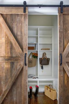 A barn wood door slides open to reveal a mudroom filled with white beadboard built in lockers fitted with shelves.