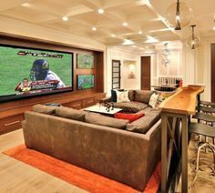 Man cave with big screen tv for the main game and 2 smaller tv's for additional games. Also love the sofa set up with the bar table and stools behind it. Would rather do other pin for the bar though!