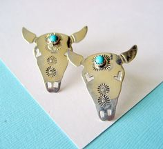 These sterling silver earrings are Navajo handcrafted. The design depicts hand stamped Buffalo skulls with bezel set turquoise stones in the heads. These earrings measure 1.25 inches tall by just under 1.25 inches wide. Post backs for pierced ears. Signed sterling with the artists hallmark.