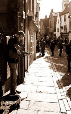 Busker in Whitby, North Yorkshire, UK (edited in sepia)