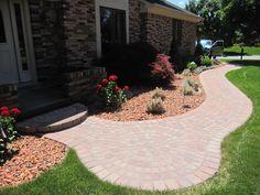 Brick paver walkway with circle step and small patio.