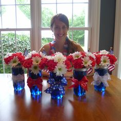Pinterest-inspired centerpiece floral arrangements, created by Dana, for our 4th of July party using mason jars, white daisies, red carnations, & red, white, & blue ribbon