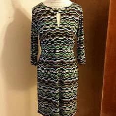 Multi-colored wavy dress 3/4 length sleeves , empire waist and keyhole neckline. 34 inches in length. Colors are black, neon green, purple, aqua and white. Hides all lumps and bumps. Back hidden zipper Emma & Michele Dresses