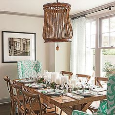 Stylish Colonial Dining Table | This space in the kitchen features a large farm table capped with punchy slipcovered wing chairs. A trio of new elongated six-over-one windows floods the area with light.