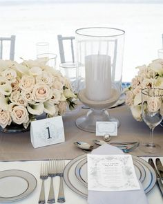 For Elizabeth and Colin's seaside tablescape, arrangements of white roses and calla lilies were set off by candles nestled into sand-filled glass vessels.
