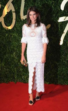 Natalie Massenet wears an Alessandra Rich white lace dress with middle split and scalloped hem. She styled the column dress with a gold studded Alexander McQueen clutch and rose-detailed sandals.