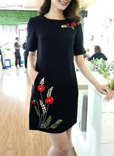 Neck and hem bright floral embroidery on a dark plain dress.