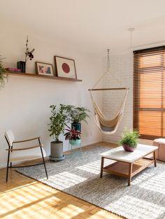 Sala ampla integrada e jovem com sofá duplo, poltrona, rede pendurada no teto, pilar aparente, plantas e prateleiras. #inaarquitetura #reformadeapartamento #sala #saladeestar #Minimalista