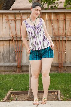 Purple/white/green tank top, blue ikat short-shorts, pineapple sandals.