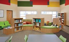 Incorporation of shelving with furniture - great idea. If space permitted this idea could be taken on to have the flow of the units as another symbolic view of Fiction or shapes that children enjoy