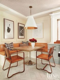 A custom banquette and table by Willey Design LLC join Restoration Hardware Buckle chairs in this breakfast nook.