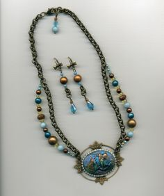 This is my August 2015 Ocean Challenge piece. The cameo is hand painted, surrounded by rhinestone cup chain on a leaf pendant. Lovely bow earrings complement this piece with chain that matches the necklace. Most pieces from B'Sue Boutiques. For sale $50.00.