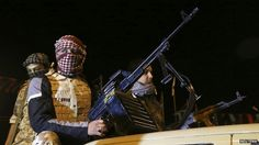 Members of a heavily armed militia group hold their weapons in Freedom Square in Benghazi on 18 February 2014