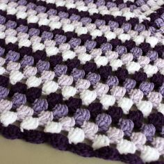 Using a puff stitch to add a feminine touch, I made this granny-style crocheted baby blanket in ombre shades of purple.