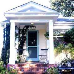 Ranch with a Charming Stoop--Dignified and rich, the covered stoop of this ranch-style home is accented by cheery yellow and turquoise paint, red bricks, and pots of bright flowers. The outdoor ceiling is painted turquoise to emulate the sky and match the front door.