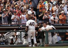 San Francisco Giants' Madison Bumgarner (40) is congratulated upon his return to the dugout after hitting a grand slam off Arizona Diamondbacks' Matt Stites in the sixth inning of a baseball game Sunday, July 13, 2014, in San Francisco. (AP Photo/Ben Margot)