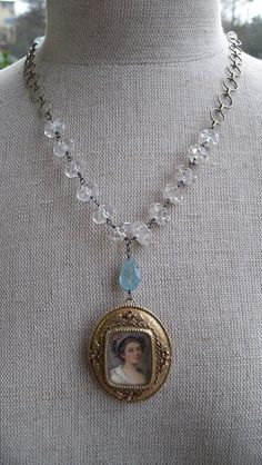 A sweet, romantic portrait framed in brass and hanging from a mix of vintage hand cut Austrian rock crystal, and faceted aquamarine. Aquamarine