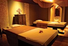Beautiful Thai themed spa with gold wallpaper, silk cushions and aromatherapy all in temple-like setting