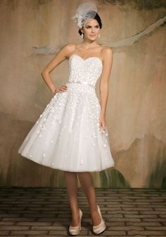 Drop waisted tea length gown has sweetheart neckline and is embellished with all over petite 3 dimensional flowers.  It has a small satin ribbon and bow at the natural waist.