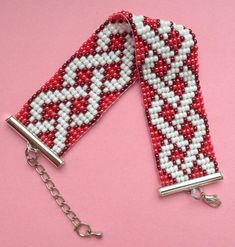 Stylish, made ​​of Czech beads in shades of pearl-white and coral-red with an extension chain allowing the bracelet to fit any wrist. The colorful pattern give Loom Bracelet Patterns, Bead Loom Bracelets, Bead Loom Patterns, Beaded Jewelry Patterns, Beading Patterns, Bead Loom Designs, Motifs Perler, Seed Bead Jewelry, Loom Beading