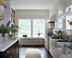 The kitchen is sheathed in subway tile from Urban Archaeology; the pendant lamps over the sink are by Rejuvenation, the range is by La Cornue with a hood by Broan, and the sinks from Rohl have fittings by Newport Brass.     - ELLEDecor.com