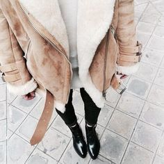Street style: Brown fluffy jacket is warm for autumn / winter. Looks chic paired with black ripped skinny jeans and boots