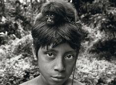 by Sebastião Salgado - Um filhote de macaco, capturado e domesticado pelos awá, sobre a cabeça do jovem Yahara.