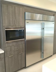 microwave/floor to ceilling cabs in grey.    Photo of Jamie's Kitchen Cabinets and Bath - Rosemead, CA, United States. Sub Zero double refrigeration was integrated into this bank of wall cabinets along with a built in Wolf Microwave.