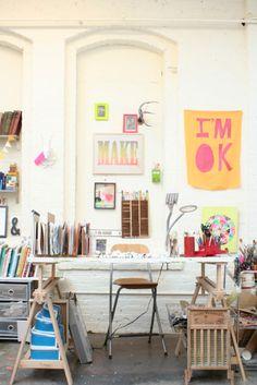 Cavaletes como escrivaninha e muitos pôsteres na parede.