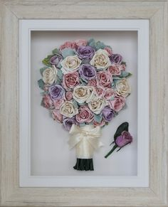 A classic and timeless round posy preserved wedding bouquet of ivory, pink and purple pastel roses scattered with dusty miller. The ivory satin ribbon and bow on the stems adds a sweetness and compliments the roses. The Driftwood frame brings the whole look together with a vintage and feminine feel.