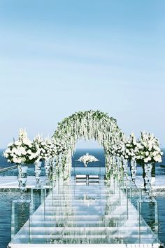 White floral arch and flowers for a wedding by the sea // The Wedding Scoop's Top 10 Florals and Decor of 2015