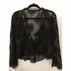 New York & Co lace top - like new Black Lacey (stretch) overlay with sequins- ties in front with satin ribbon. Arms have slight bell design. Never worn. New York & Company Tops Blouses