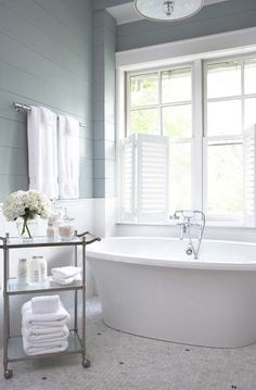Beautiful Bathroom with gorgeous tub  cart with bathroom accessories! Love the wood plank walls  colors !