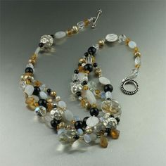 Catch the light and admiring glances with this Onyx and Crystal Quartz necklace. Round smooth Onyx beads are are mixed throughout a mix of faceted Citrine, Moonstone, Gold Freshwater Pearls, Goldstone Quartz, and Opal Glass gemstone beads. Fine Silver beads accent the necklace with a touch of sparkling shine.