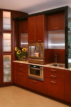 A Lovely Modern Kitchen with what appears to be cherry cabinets, and a built-in coffee center appliance by Jenn Air made of stainless steel. Modern, beautiful, and practical!