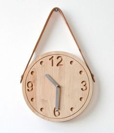 Raw wood wall clock with a simple face. Love the effect of the hanging strap.