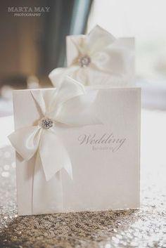 De recuerdos de papel.  Invitaciones de boda de lujo de tarjeta perla con mejor calidad doble cara cinta de raso que está disponible en aproximadamente 80 colores con un adorno de diamante de calidad grado A.  Especificaciones  • Tarjeta de Marfil nacarado o blanco cristalino • Emparejar nacarado Inserte • Totalmente personalizado con tus datos • Disponible en tamaños de 14 cm x 14 cm y 14,5 cm x 20 cm • Envoltura de marfil o blanco • Opción de 80 tonos de cinta • Elección de Diamante o…