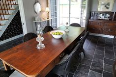 Dining room with long wood table, wicker chairs.