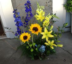 Flower school garden style design with delphinium, sunflowers, snapdragons, lilies, button poms, curly willow, ruscus, leather leaf fern and galax leaves