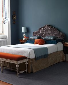 A slate blue wall creates a rich, gorgeous backdrop for velvet orange pillows and shiny accents in varying shades of blue. Crisp white curtains with coordinating stripes help to pull it all together.  Source