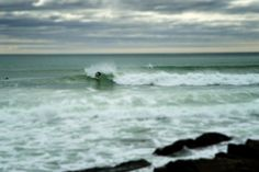 A March surfer catching waves at Ruggles in Newport, RI